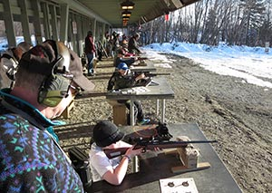 Seated students shoot while instructor watches
