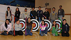 Group of young archers in a classroom with their bows