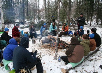 Group of people sitting around a fire in the winter