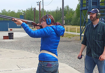 Girl shooting while man watches