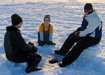 Three people ice fishing