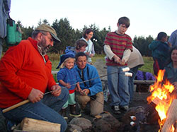 camp participants and instructors roast marshmallows over a campfire