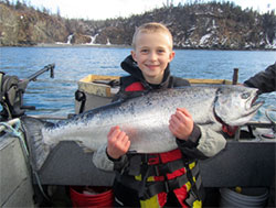 A boy holding a large Chinook salmon.