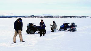 ice fisherman fish nearby their ATV and snowmachine