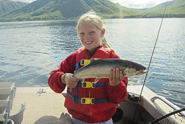 young girl smiles while holding up her salmon catch