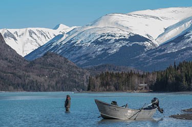 An angler fishes the Kenai River with scenic snow-covered mountains in the background