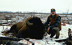 A hunter kneeling next to a bison he brought down