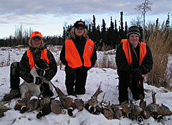 Three young hunters with a bunch of pheasants lined up