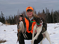 A young hunter and her dog with a pheasant she brought down