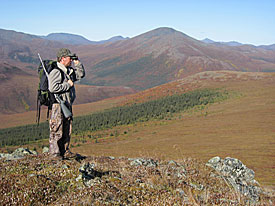 Photo of a man looking through a pair of binoculars