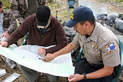 Photo of a state trooper and a guide looking at a map