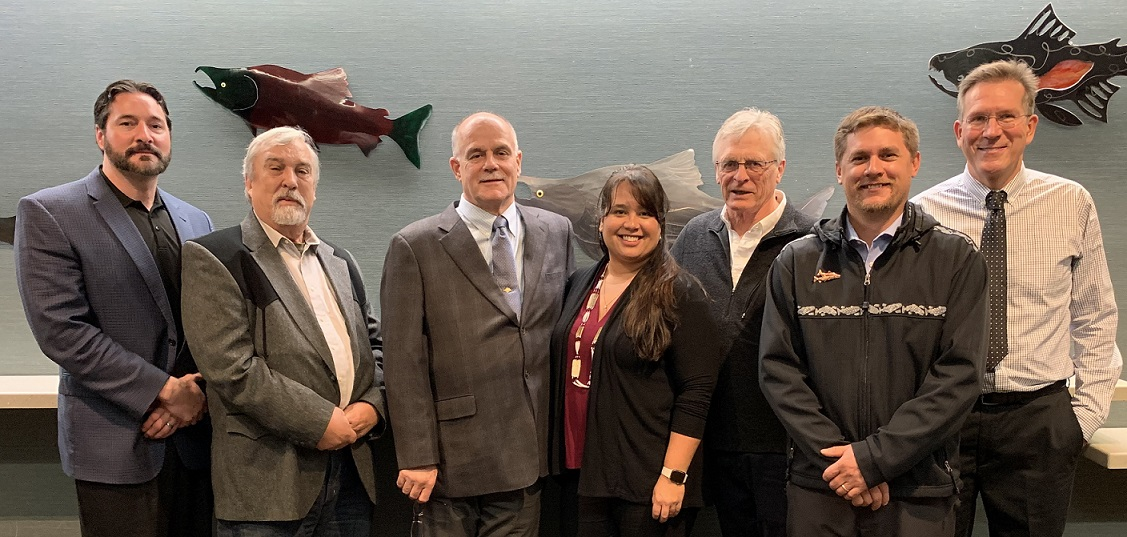 Group photo October 2019; board members standing in front of metal fish art